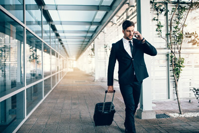 Handsome young man on business trip walking with his luggage and talking on cellphone at airport. Travelling businessman making phone call.