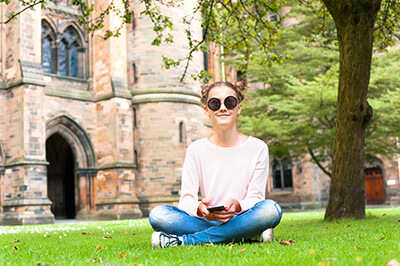Young lady with mobile phone sitting on the grass in Glasgow University garden looking at camera. Summertime outdoors.